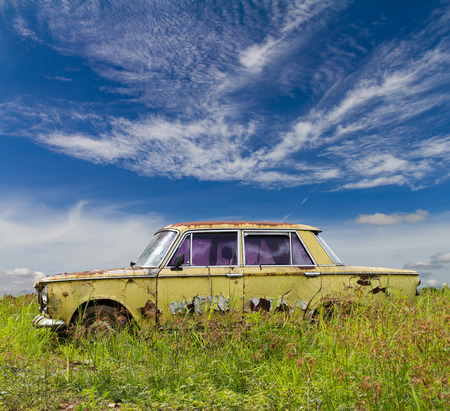 View older sedan, green rust is still in the grass, which has a cloudy sky as a backdrop. Stock Photo