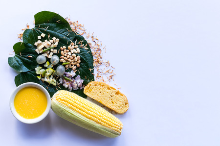 Leaf-Wrapped Bite-Size Appetizer with sweet corn juice and its pods, as well as bread and other healthy foods.