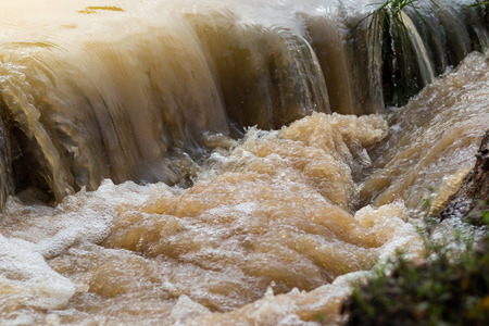 turbid: Close-up image of turbid water flowing like a waterfall on flooded canal in rural Thailand.