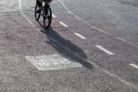 one lane road sign: Look behind the silhouette of a cyclist on a curved road with a symbol on a paved road.