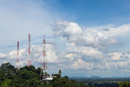 La vue des poteaux de télécommunication est montée sur un grand buisson d'arbre avec des nuages ??de ciel comme toile de fond pendant la journée.