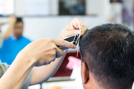 Close-up of a Thai man with a barber using clippers with black hair comb in a shop. Stock Photo