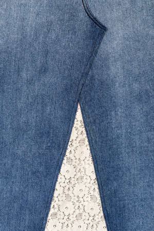 Close-up background of fabric, jeans, which was modified, sewn together with white Thai motifs.