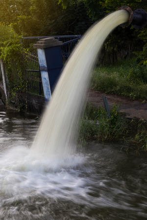 groundwater: View of the fast flowing stream and force from the high steel pipe to drain into the canal.