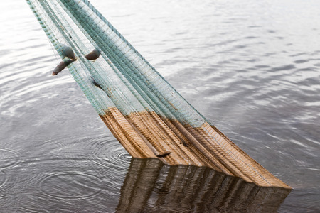 Close-mesh nets to catch fish, which was pulled from the water by fishermen carefully.