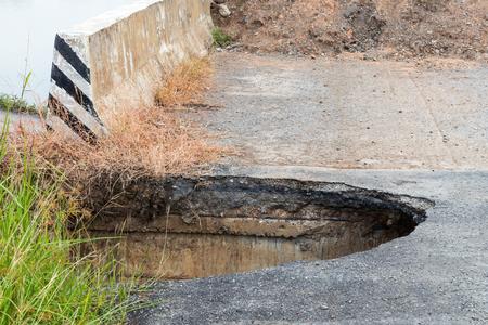 田舎のコンクリート橋近く侵食された舗装道路下の深穴のクローズ アップ。 写真素材