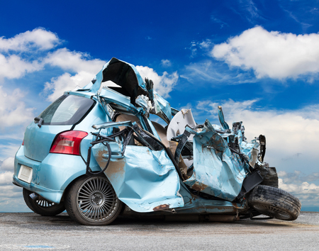 The light blue sedan was demolished by a collision with another strong vehicle, which had a sky background.