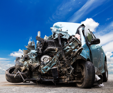 Close-up of front passenger car, which was demolished by accident, collided with another vehicle, had the sky as the background.
