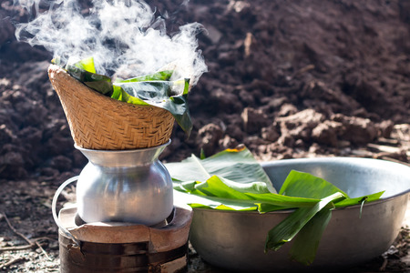 Steam the sticky rice in a bamboo basket with smoked banana leaves on the charcoal stove on the ground.