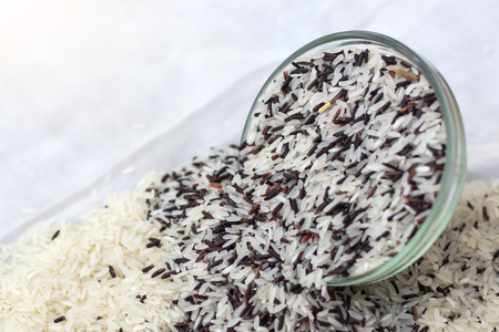 Close-up of white and black grains, which are poured and stacked, overflow from the glass cup on a white cloth. Stock Photo