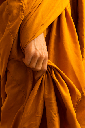 Close-up view of hands of Buddhist monks, who are robbing their robes with gentle politeness.