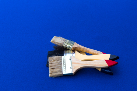 Close-up paint brushes painted all four, cleaned and stacked overlapping on a blue fabric background.