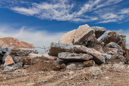 Close-up image of debris, large concrete slabs, which are dismantled from the road, clouds and sky as the backdrop. Stock Photo