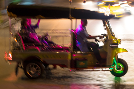 Close-up of a taxi driver on a streetcar tricycle on a night road, often seen in the capital of Thailand.