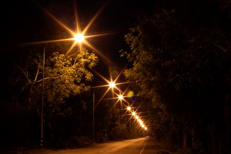 Vista panoramica dalla scarsa illuminazione da molte lanterne su una strada di campagna alberata al crepuscolo. Archivio Fotografico
