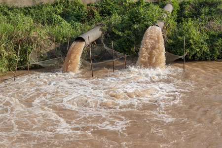 Brown turbid streams are ejected from both large sewers through a fishing net into the river.