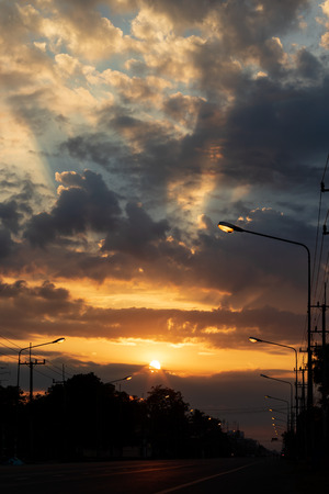 Siluette, the sun rising in a cloudy, dusk, early in the morning, above the Thai countryside, which has a residence with trees and a lamp post mounted on the side of the road. Stock fotó