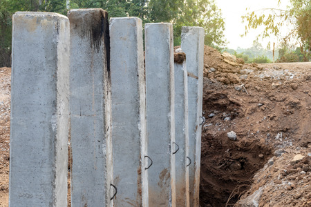 Close-up view of many concrete column poles lined up in the soil of the road which has been excavated to build a bridge in the Thai countryside.