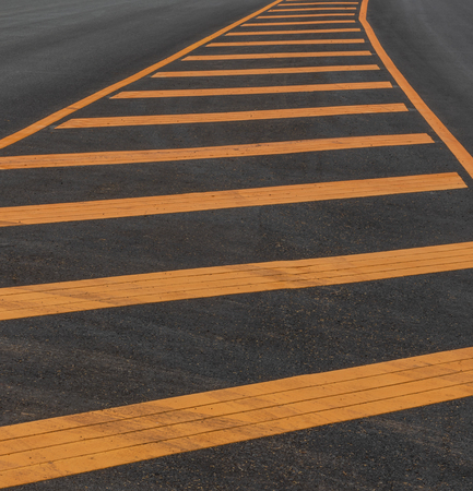 Close-up image of a new road surface background with yellow painted strips and dirt traces of wheels. Stock Photo
