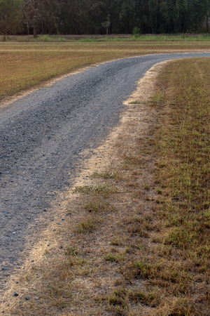 A view of a crushed stone road that stretches and curves on a park with only grass in the countryside of Thailand. Stock Photo