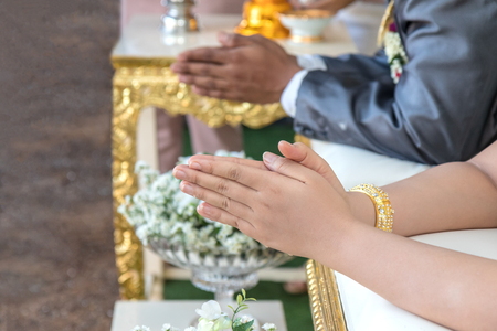Close up beautiful bride, groom, hands clasped pay homage to wait for the blessed water secretion in the wedding ceremony of one of rural Thailand. 스톡 콘텐츠