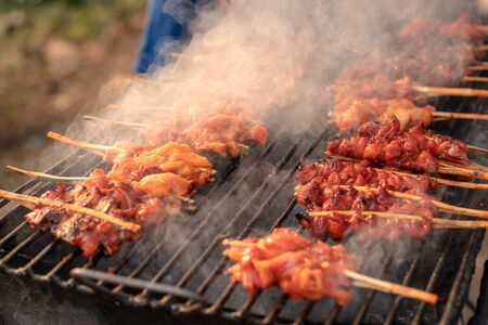 Close-up picture of grilled chicken skewers on an old iron grill and charcoal stove causing smoke Foto de archivo - 129255564