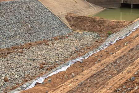 The view of many granite blocks in the wire mesh is constructed as a wall adjacent to the coastal soil near the overflow to prevent water erosion in the canal.