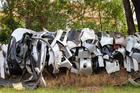 A view of a lot of bumper car debris that gather in a row on the countryside, close to a tree outside a car garage.
