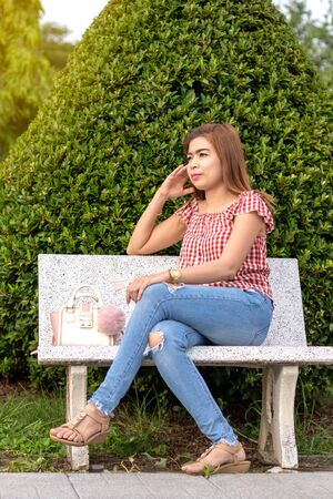 A beautiful Thai woman sitting and pondered, staring at something on a marble chair near a green bush in a park in Thailand. Фото со стока