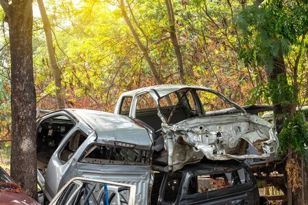 Close-up view of the car frame which has been damaged by an accident was dumped between a tree in the countryside near the car garage.