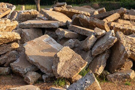 Vue rapprochée des gros débris de béton laissés sur la campagne avec la lumière du soleil pendant la journée.