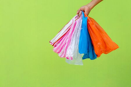 Many colorful plastic bags that were crumpled in the hands of a man with a green concrete wall in the background. 写真素材