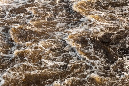 The background texture of the spreading waves of turbid brown water circulating swiftly near the dam in the Thai countryside.