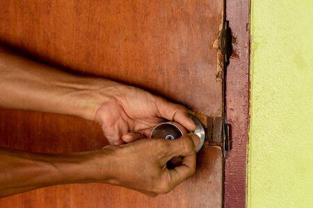 Primer plano, ambas manos sosteniendo el pomo de la puerta de madera vieja, que está cerrada y dañada, necesita ser reparada. Foto de archivo