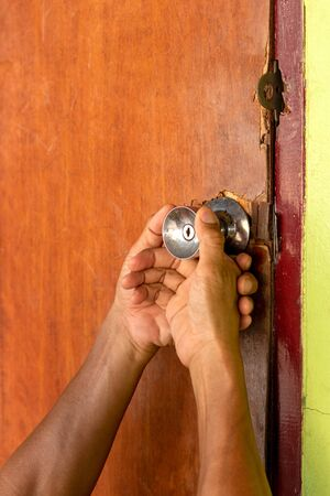 Close-up, both hands holding the old wooden door knob, which is closed and damaged, needs to be repaired.