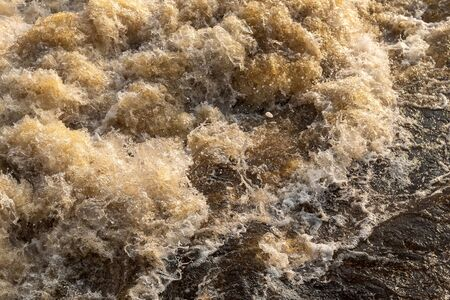 Close-up of the turbulent surface of the water surface, violently turbulent near the opening of the dam and the afternoon sunlight in the Thai countryside.