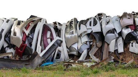 Isolated pieces of front bumper scraps, which were collected from the garage and dumped on grassy ground.