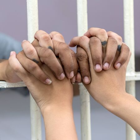 The close-up image of the hands of the two young women prisoners whose tattoos are holding them together during the cage. The white prison room shows concern.