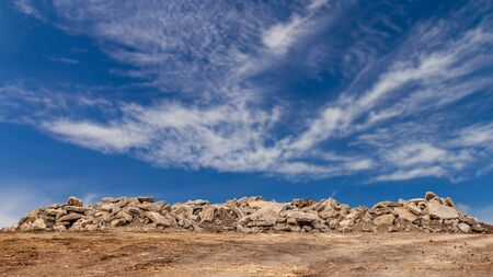 Wide view, many debris from old concrete roads that were demolished, destroyed and placed on the ground with clouds, blurred sky as a backdrop. Reklamní fotografie