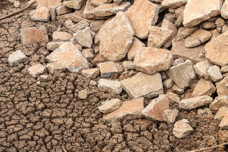 Close-up view of concrete road debris that has been left to sink in the mud and dry soil. Reklamní fotografie