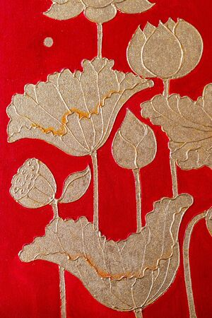 The background of the lotus flower and gold leaf is a beautiful art against the red wall backdrop.