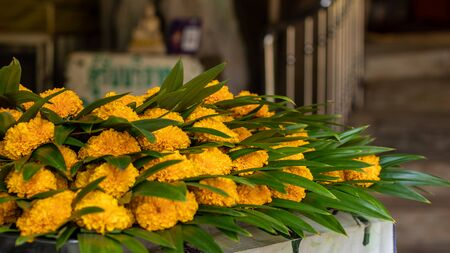 Marigold bouquets and pandan leaves are stacked on the table in one of the temples in the Thai countryside. 版權商用圖片