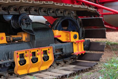 Close-up of new colorful track steel wheels, which are part of the combine harvester, commonly seen in rural Thai agricultural areas.