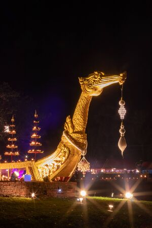 Close-long boat made of foam, which resembles a golden swan beautifully decorated with lights and candlelight at night festival of Thailand.