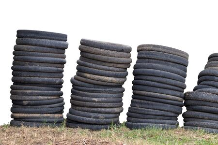 Isolate many old motorcycle wheels stacked in a row, were dumped on the ground, filled with hay.