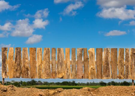 The low view, a fence made up of tree bark lined up with clouds in the countryside during the daytime as a backdrop.