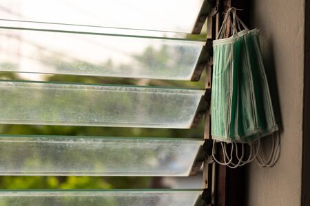 Many green sanitary masks are hung on the wooden frames of louver windows inside a house.