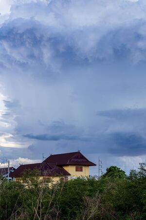 Cloudy landscape before rain will fall over a house with bushes beneath rural Thailand. Banco de Imagens