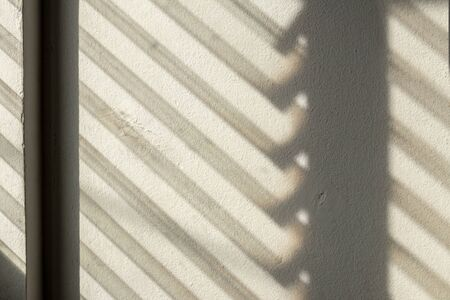The close-up background of the dark shadow of sunlight shining through the shutters to the opaque concrete walls in an old building in the early morning.