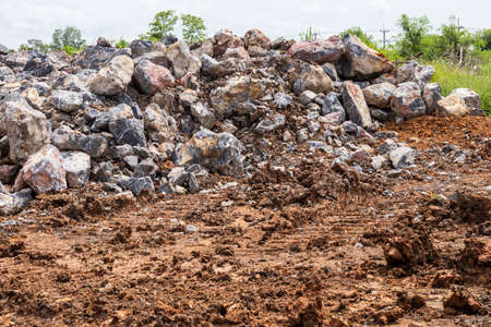 A close-up view of massive granite boulders that have been piled together on the ground in preparation for construction in one of the rural areas of Thailand.